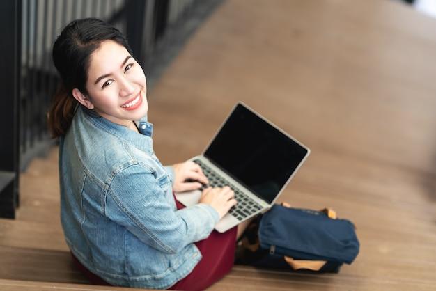 Asiatisches frauensitzen des porträtsitzens, unter verwendung des laptops, lächeln und kamera betrachtend.