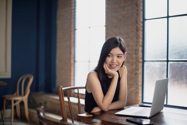 Asiatisches freiberuflich tätiges mädchen, das an der kaffeestube mit einem laptop arbeitet.