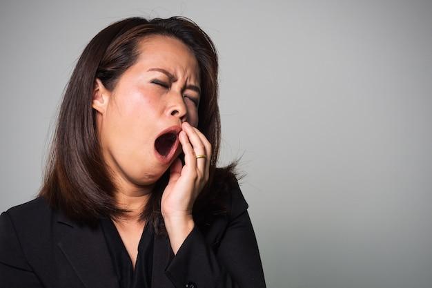 Asiatisches gähnen der erwachsenen frau. müde und schläfrige emotionen.