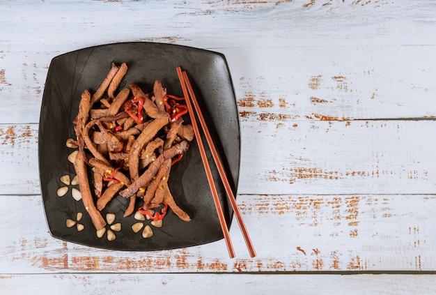 Asiatisches gegrilltes rindfleisch mit paprikapfeffer und essstäbchen.