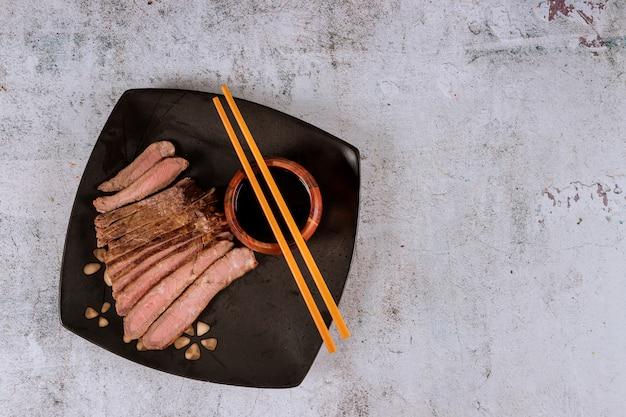 Asiatisches gegrilltes steak mit sojasoße und essstäbchen.