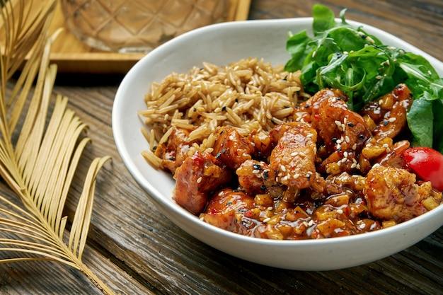 Asiatisches gericht - huhn in süß-saurer sauce mit reis-rucola-salat in einer schüssel auf einem holz. straßenessen