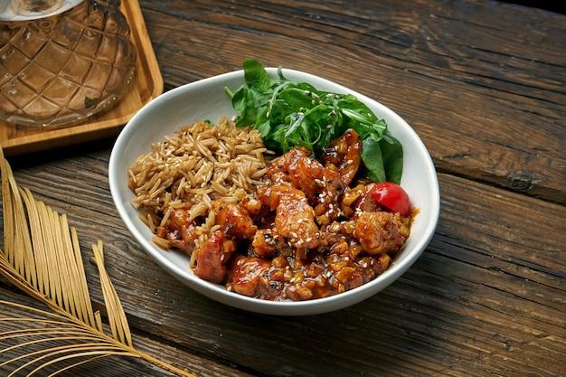 Asiatisches gericht - huhn in süß-saurer sauce mit reis-rucola-salat in einer schüssel auf einem holztisch. straßenessen