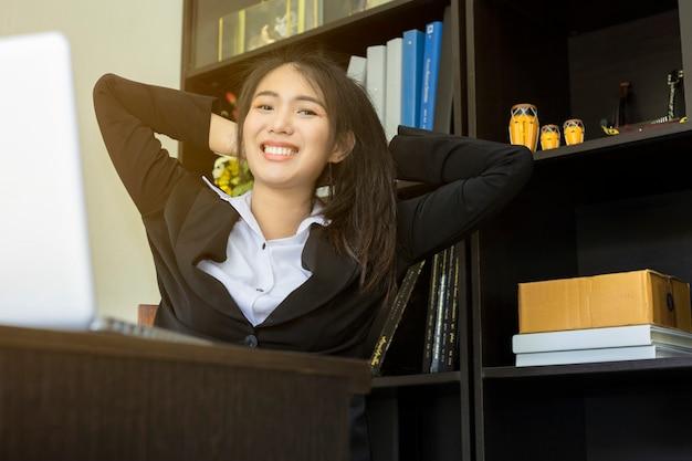 Asiatisches geschäftsfrausitzen entspannen sich mit arbeitslaptop auf dem schreibtisch im büro.