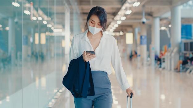 Asiatisches geschäftsmädchen, das smartphone für scheck-bordkarte verwendet, die mit gepäck zum terminal am inlandsflug am flughafen geht.