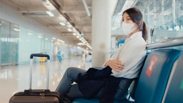 Asiatisches geschäftsmädchen mit gepäck, das in der bank sitzt, warten und partner für flug am flughafen suchen.