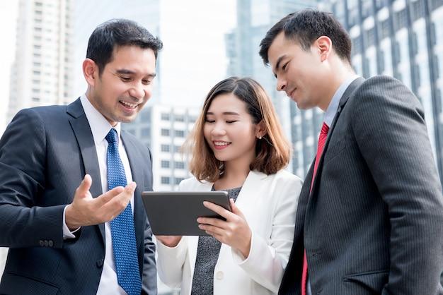 Asiatisches geschäftsteam, das draußen on-line-arbeit über tablet-computer bespricht und teilt