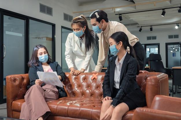 Asiatisches geschäftsteam, das gesichtsmaske trägt, die mit geschäftsplan auf ledersofa im neuen normalen büro diskutiert