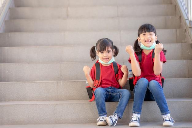 Asiatisches geschwister mit gesichtsmaske, das nach covid-19-quarantäne und sperrung wieder zur schule geht