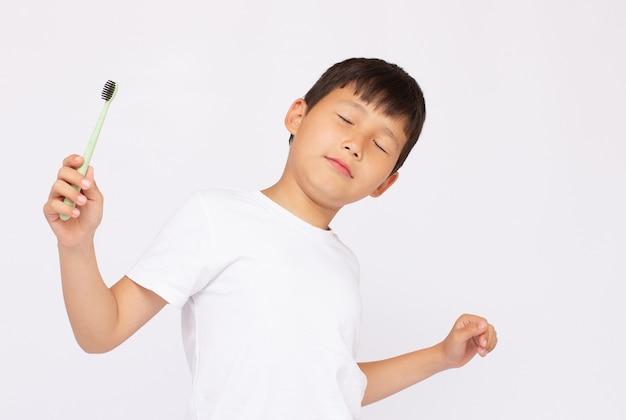 Asiatisches gesicht der nahaufnahme, kleine süße kinderjunge, die hand hält, hält zahnbürste, die er jeden tag morgens selbst die zähne putzt, auf weißem hintergrund mit kopienraum, medizinische versorgung