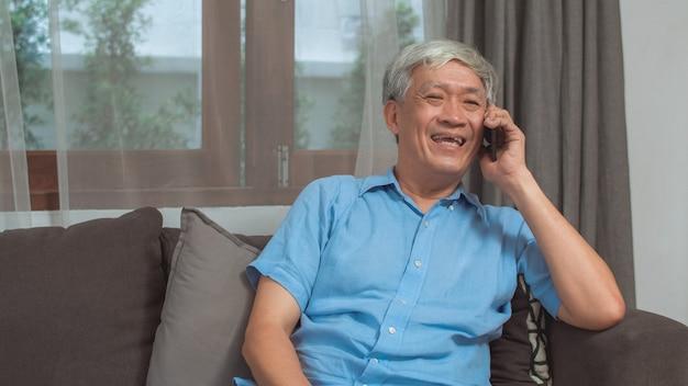 Asiatisches gespräch des älteren mannes am telefon zu hause. der asiatische ältere ältere chinesische mann, der den handy spricht mit familienenkelkind verwendet, scherzt beim auf sofa im konzept des wohnzimmers zu hause liegen.