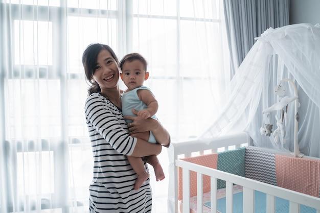 Asiatisches glückliches baby auf der krippe