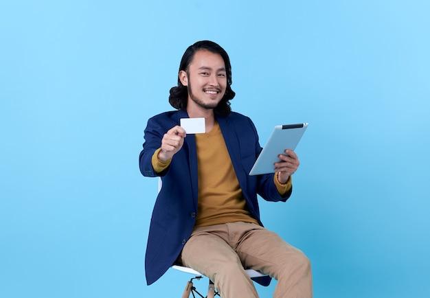 Asiatisches glückliches lächeln des geschäftsmannes, das kreditkarte zeigt und eine digitale tablette verwendet, während auf stuhl auf hellem blau sitzt.