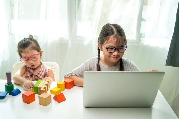 Asiatisches glückliches mädchen, das laptop verwendet, der hausaufgaben macht und online-anwendungszoom mit ihrem lehrer studiert