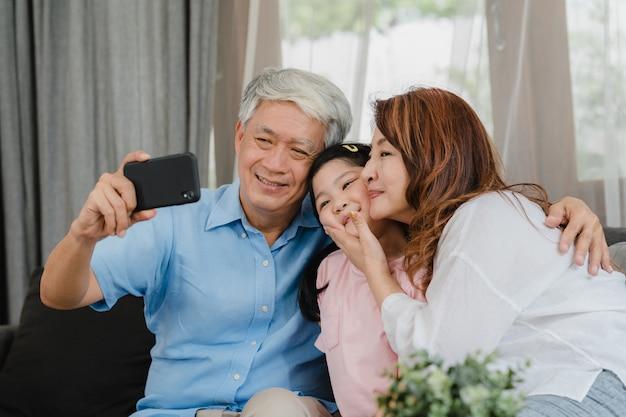 Asiatisches großeltern selfie mit enkelin zu hause. der ältere glückliche chinese, der großvater und die großmutter verbringen familienzeit unter verwendung des handys mit dem kind des jungen mädchens, das auf sofa im wohnzimmerkonzept liegt.