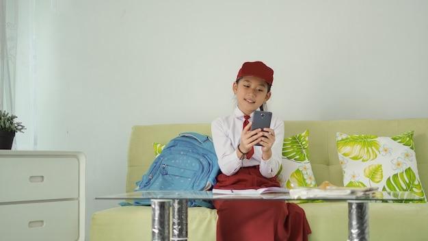 Asiatisches grundschulmädchen, das auf ihrem smartphone nach ideen für lernmaterial zu hause sucht
