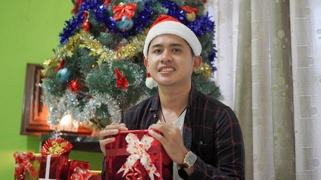 Asiatisches gutaussehendes lächeln mit weihnachtsfeiergeschenken zu hause