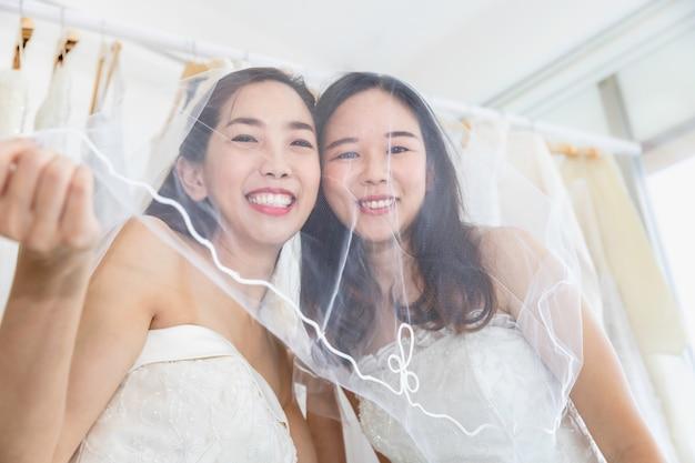 Asiatisches homosexuelles paar, das im brautkleid lächelt. konzept lgbt lesbe.