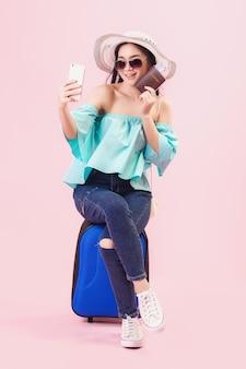 Asiatisches hübsches junges mädchen, das lächelt, trägt eine sonnenbrille und macht ein selfie mit dem smartphone, junge frauen backpacker machen ein selfie und halten einen reisepass im studio rosa hintergrund pastellrosa-tonfilter.