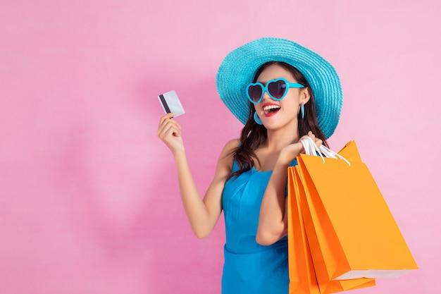 Asiatisches hübsches mädchen, das einkaufstaschen während griff-kreditkarten und sonnenbrilleseinkaufskonzept hält.
