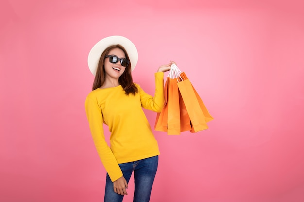 Asiatisches hübsches mädchen, welches die kaufenden orange taschen schauen weg auf rosa hintergrund, buntes einkaufskonzept hält.