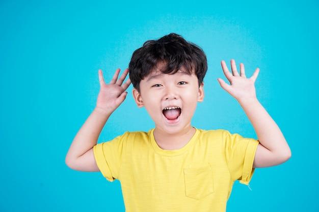 Asiatisches hübsches niedliches kleines jungenkind mit reizendem ausdruck und handbewegung zeigen