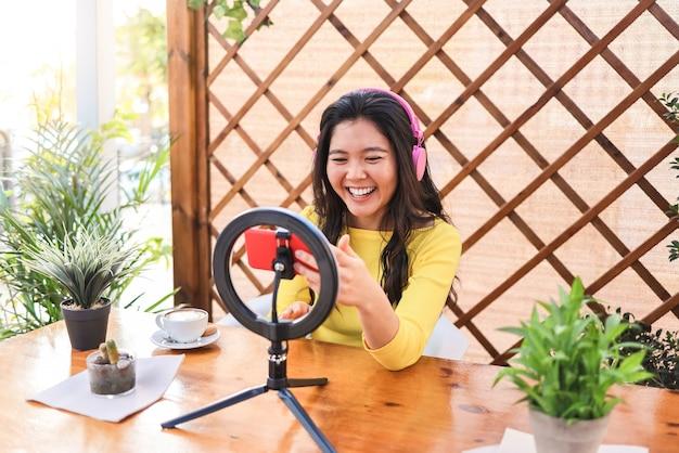 Asiatisches influencer-mädchen, das online mit smartphone-kamera draußen im restaurant strömt