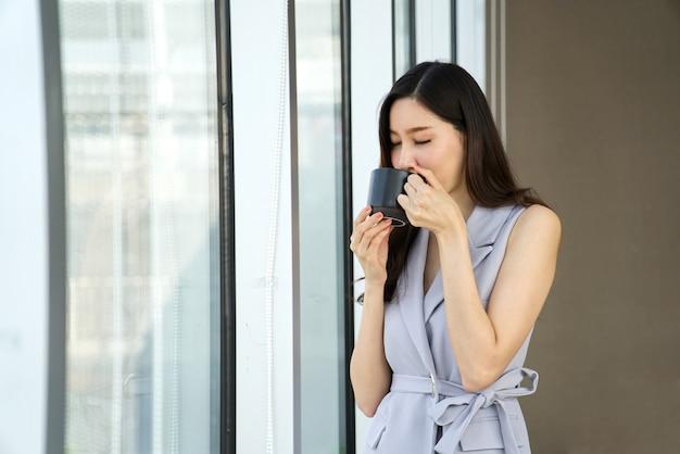 Asiatisches intelligentes schönes mädchen, das einen rest durch das trinken des tasse kaffees steht nahe dem fenster im büro spricht.