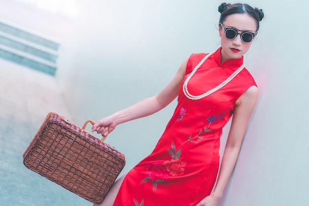 Asiatisches japanisches chinesisches mädchen mit asiatischem reisekonzept der hölzernen gepäckweinlese
