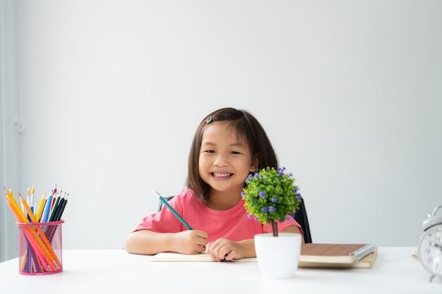 Asiatisches jüngeres kind lernt und bestätigt allein zu hause