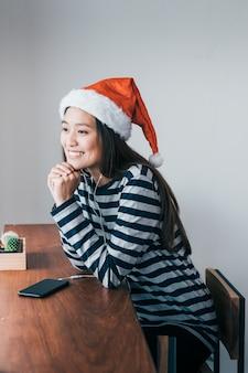 Asiatisches jugendlicheabnutzungs-sankt-hut- und -lächelngesicht, das ihr kinn auf ihren händen nahe fenster in der weihnachtspartei am café stillsteht