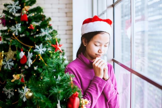 Asiatisches jugendlichmädchen schloss ihre augen und faltete ihre hand im gebet, um in der weihnachtsfeier zu wünschen