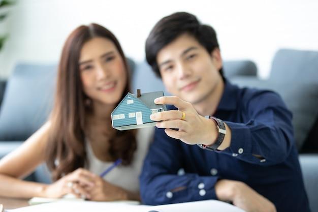 Asiatisches jugendpaar plant, sein zukünftiges haus mit seiner frau in der modernen wohnung zu bauen.