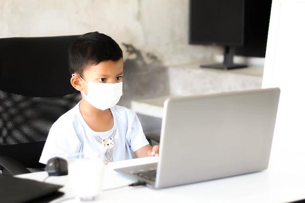 Asiatisches jungenkind, das am tisch mit laptop und medizinischer gesichtsmaske sitzt und sich zur schule vorbereitet. online-bildungskonzept. online-video-telefonkonferenz unterrichtsstunde.