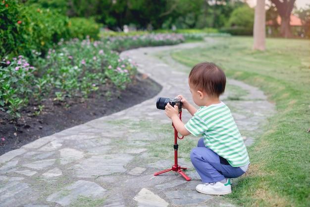 Asiatisches jungenkind, das foto unter verwendung einer kamera u. des stativs am park nimmt