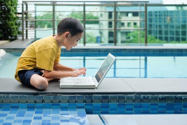 Asiatisches jungenkindersitzende seite des pools und gebrauchlaptop für bildung