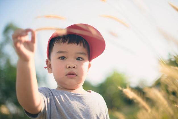 Asiatisches jungenspielen im freien mit trockenen gräsern