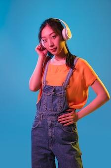 Asiatisches junges frauenporträt auf dunkler wand im neonkonzept des gesichtsausdrucks der jugendverkaufsanzeige der menschlichen gefühle