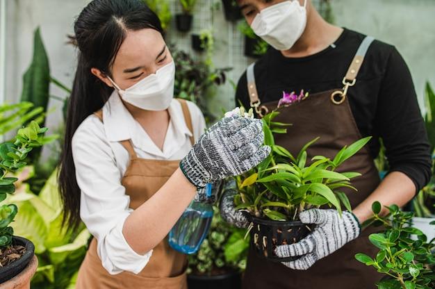 Asiatisches junges gärtnerpaar des porträts, das schürze trägt, verwendet gartengeräte und hilft, die zimmerpflanze im geschäft zu pflegen