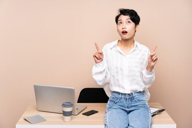 Asiatisches junges geschäftsmädchen an ihrem arbeitsplatz, der mit dem zeigefinger eine große idee zeigt