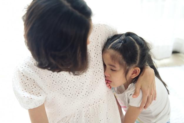 Asiatisches junges kleines mädchen weint nahe bei ihrem elternteil und ihrer mutter, die trösten, indem sie leicht auf kopf berühren.