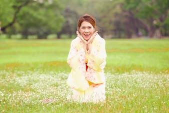 Asiatisches junges Mädchen, das einen Kimono im natürlichen grünen Gras trägt.