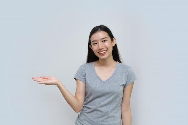 Asiatisches junges mädchen, das etwas auf beiden flachen händen für ähnliche wahl des produktes anzeigt