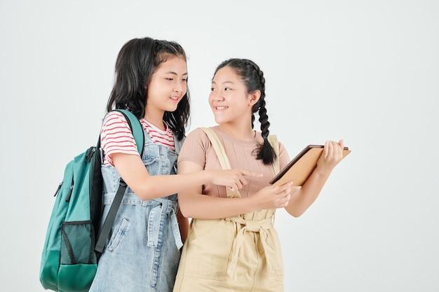 Asiatisches junges mädchen, das freund bittet, ihr bild auf dem bildschirm des digitalen tabletts zu zeigen
