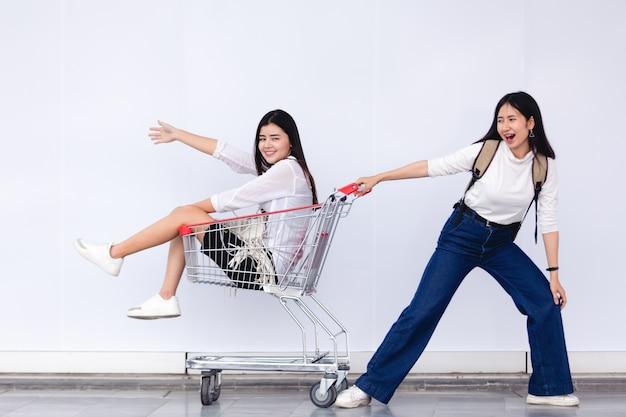 Asiatisches junges mädchen, das im warenkorb für marketing-konzept sitzt