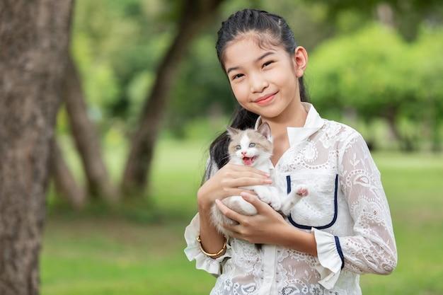 Asiatisches junges mädchen, das kätzchen im park hält