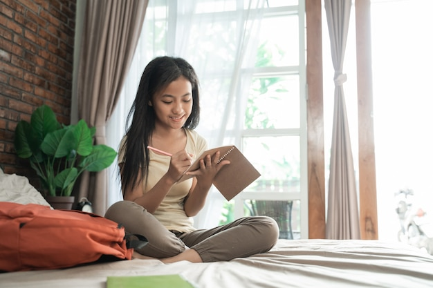 Asiatisches junges mädchen, das zu hause studiert
