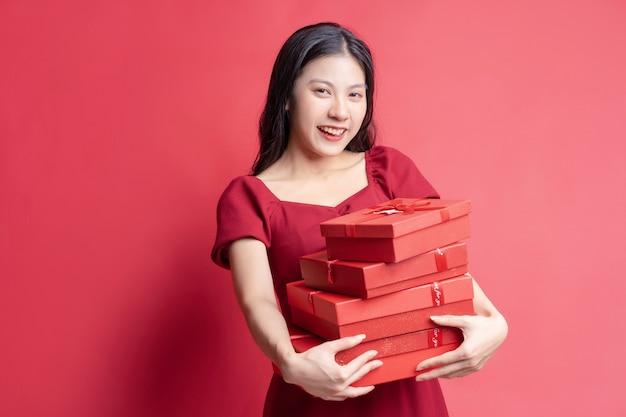 Asiatisches junges mädchen im kleid, das rote geschenkbox mit fröhlichem ausdruck im hintergrund hält