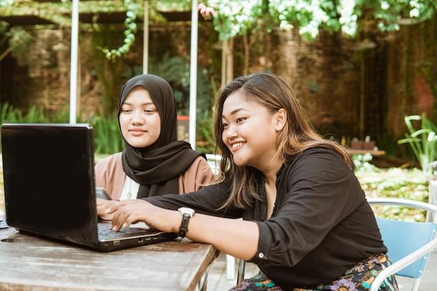 Asiatisches junges mädchen mit ihrem laptop und tablet-pc