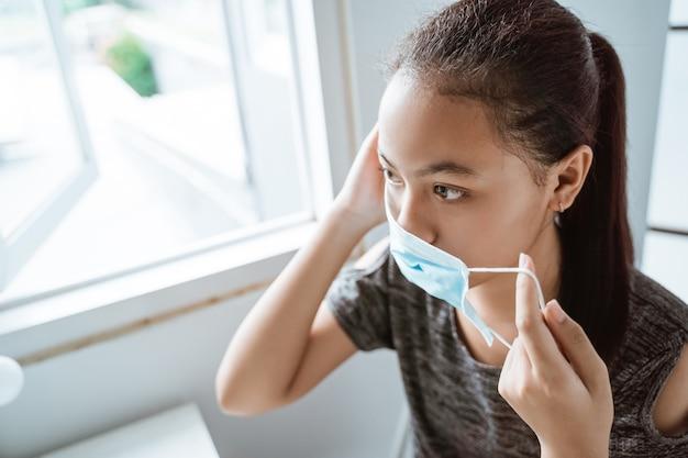 Asiatisches junges mädchen trägt eine medizinische maske, während es am fenster im raum sitzt